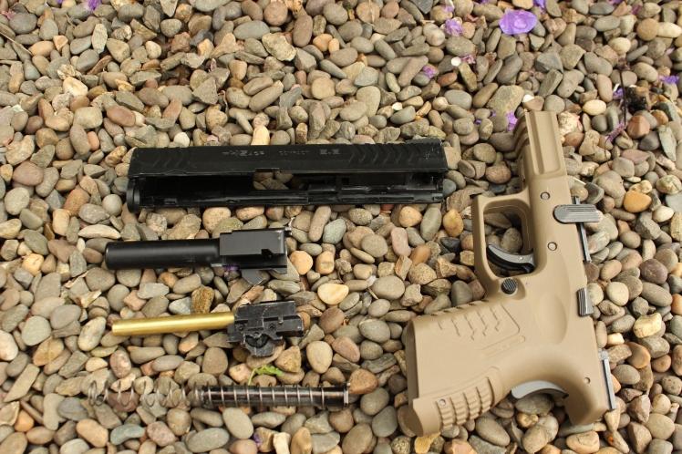 The pistol broken down. The hop adjustment can be seen here.